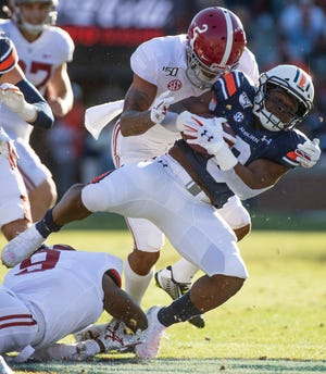 Auburn running back Shaun Shivers (8) is stopped by Alabama defensive backs Patrick Surtain, II, (2) and  Jordan Battle (9) in first half action in the Iron Bowl at Jordan-Hare Stadium in Auburn, Ala., on Saturday, November 30, 2019.