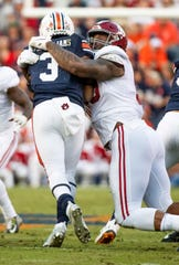 Alabama defensive lineman Raekwon Davis (99) stops Auburn running back DJ Williams (3) in first half action in the Iron Bowl at Jordan-Hare Stadium in Auburn, Ala., on Saturday, November 30, 2019.