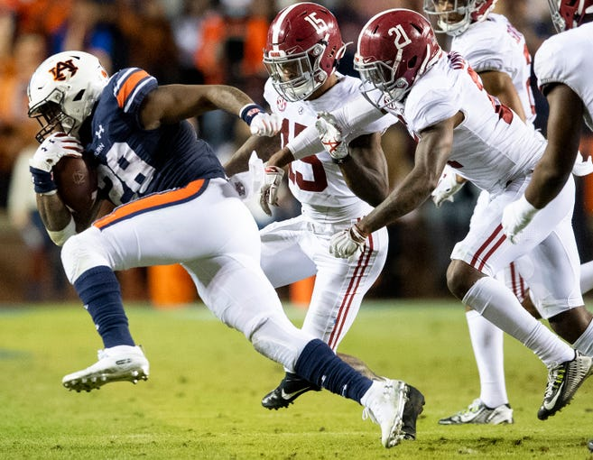 Auburn running back JaTarvious Whitlow (28) gets by Alabama defensives back Xavier McKinney (15) and Jared Mayden (21)in second half action in the Iron Bowl at Jordan-Hare Stadium in Auburn, Ala., on Saturday, November 30, 2019.