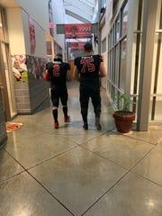 Ball State redshirt senior linebacker Jacob White and redshirt senior offensive lineman Danny Pinter walk together.