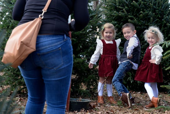 Kelsey Galkus, left, takes a photograph of her children Harper, 3, second from left, Brayden, 5, and Avery, 3, in front of trees at the Santa's Trees lot Sunday, Dec. 1, 2019, in Franklin, Tenn.