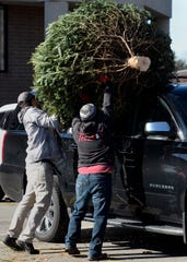 Scott Jordan, left, and Kevin Trevino of Santa's Trees load a Christmas tree onto a vehicle on Sunday, Dec. 1, 2019, in Franklin, Tenn.
