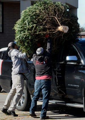 Scott Jordan, left, and Kevin Trevino of Santa's Trees load a Christmas tree onto a vehicle on Sunday, Dec. 1, 2019, in Franklin, Tenn.