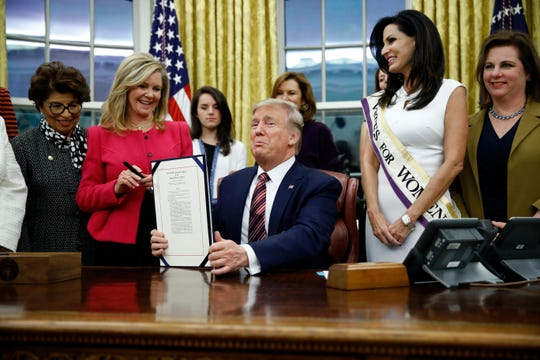 President Donald Trump displays the Women's Suffrage Centennial Commemorative Coin Act during a bill signing ceremony in the Oval Office of the White House, Monday, Nov. 25, 2019, in Washington. (AP Photo/Patrick Semansky)