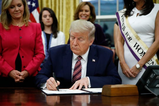 President Donald Trump signs the Women's Suffrage Centennial Commemorative Coin Act during a bill signing ceremony in the Oval Office of the White House, Monday, Nov. 25, 2019, in Washington. (AP Photo/Patrick Semansky)