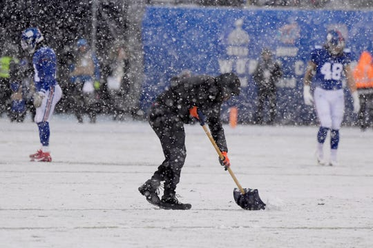 A man shovels the field during the first half of an NFL football game between the New York Giants and the Green Bay Packers, Sunday, Dec. 1, 2019, in East Rutherford, N.J. (AP Photo/Bill Kostroun)