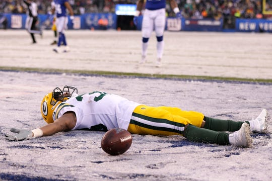 Green Bay Packers' Aaron Jones makes a snow angel after scoring what he believed to be a touchdown during the second half of an NFL football game against the New York Giants, Sunday, Dec. 1, 2019, in East Rutherford, N.J. The touchdown was nullified by a penalty. (AP Photo/Adam Hunger)