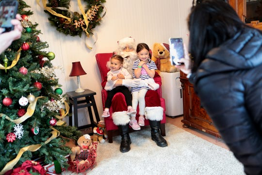 Two-year-old Annie Burke, left, and her sister Elle Burke, 4, both of Redwood City, smile for a photo with Santa at Gingerbread Lane, a free Saturday event, held at Old Town Artisan Studios in La Quinta, Calif., on November 30, 2019.
