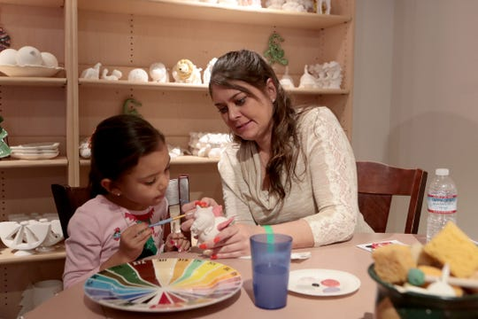 Art is a great way to keep kids entertained during the coronavirus lockdown. Here, Kylie Hayes, 6, and her mom, Kristen, both of Palm Springs, paint a ceramic figure at Gingerbread Lane on November 30, 2019.
