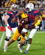 Arizona State Sun Devils defensive back K.J. Jarrell tackles Arizona Wildcats quarterback Khalil Tate (14) during the Territorial Cup at Sun Devil Stadium in Tempe on November 30, 2019.