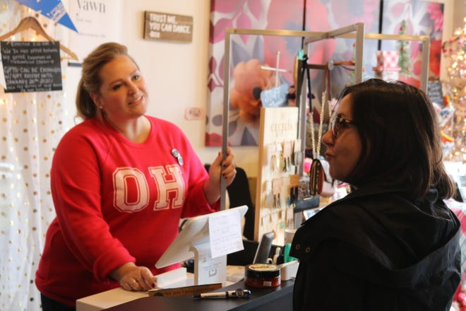 "Abbie Fox, left, owner of LakeLynn Design, a local boutique at 129 Madison St., talks with a customer on ""Small Business Saturday."""