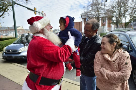 Mike Lowery, as Santa, greets a little boy who spotted him while walking on Memorial Square in Chambersburg on Nov. 14, 2019.