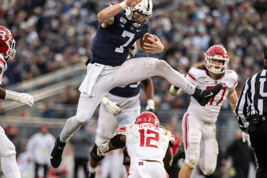 Penn State quarterback Will Levis (7) hurdles Rutgers defensive back Christian Izien (12) in the first quarter of an NCAA college football game in State College, Pa., on Saturday, Nov. 30, 2019. (AP Photo/Barry Reeger)