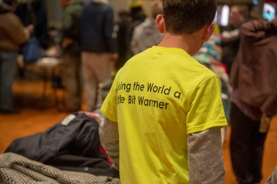 "Coats of Friendship board members wore neon yellow shirts that says they pledge to ""make the world a little bit warmer."""