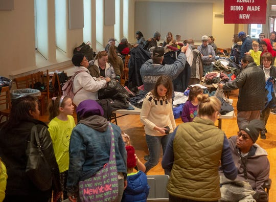 Groups of people went through tables of coats and other winter clothing at the coat distribution at Union Lutheran Church on Saturday, Nov. 30, 2019.