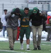 Bishop Manogue's Zeke Lee gets helped off the field while taking on Liberty during their playoff football game in Reno on Nov. 30, 2019.
