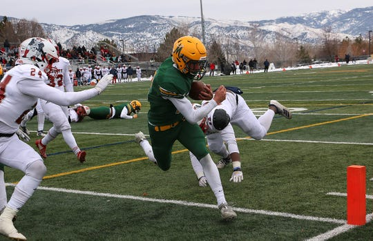 Bishop Manogue's Drew Scolari (12) scores while taking on Liberty during their playoff football game in Reno on Nov. 30, 2019.