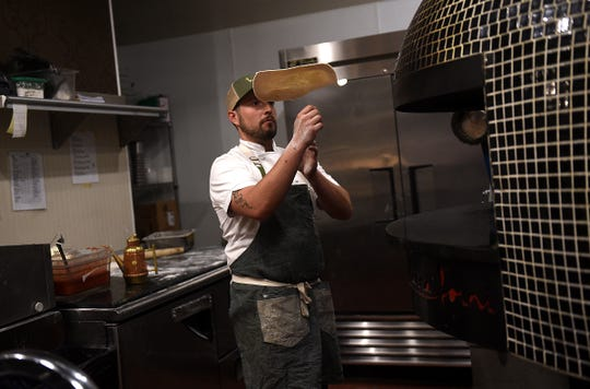 Chef Geoffrey Caliger, who runs Liberty Food & Wine Exchange in downtown Reno, works the restaurant's wood-fire pizza oven.