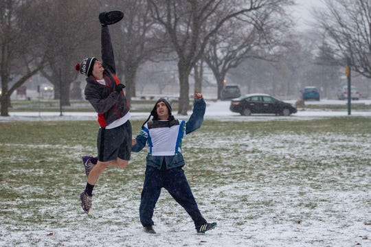 Despite cold temperatures and a frigid mix of snow and ice falling down, Scott Seyboth, left, and Patrizio Biondo met up with a small group of friends at Cobbs Hill Park to play ultimate frisbee. The Greater Rochester Area Disc Association plays every Sunday at the park -- no matter the weather, they said.