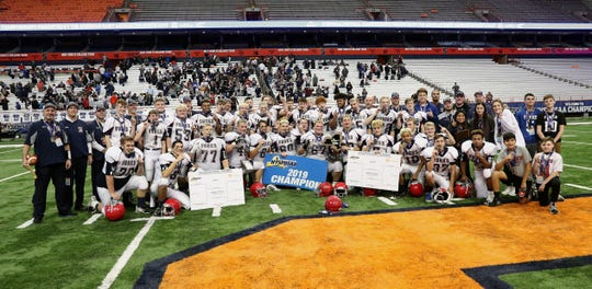 Players and coaches gather for a group photo after beating Schuylerville 38-14 for the Class B state championship.