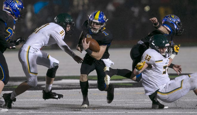 Sutter Union's Cory McIntyre, center, runs past Paradise's Josh Alvies, left, and Ashton Wagner, right, during the first quarter of a Northern Section Division III high school football playoff game in Yuba City. Paradise had an undefeated season and made it to the section championship game a year after the deadliest wildfire in California history that killed dozens and destroyed nearly 19,000 buildings including the homes of most of the players.