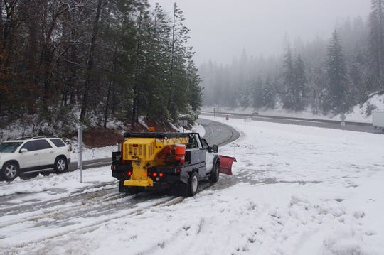 A snow plow gets ready to clear Gilman Road north of Redding on Sunday.
