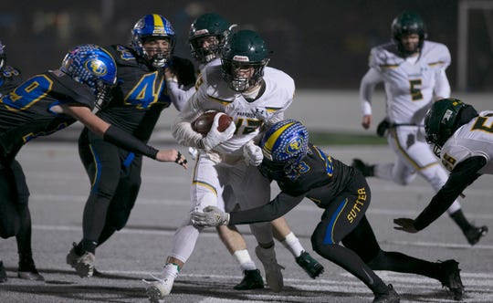 Paradise running back Tyler Harrison, center, is tackled by Sutter Union cornerback Roman Resendez during the first half of a Northern Section Division III high school football playoff game Saturday, Nov. 30, 2019, in Yuba City, Calif. Paradise had an undefeated season and made it to the section championship game a year after the deadliest wildfire in California history that killed dozens and destroyed nearly 19,000 buildings including the homes of most of the players.