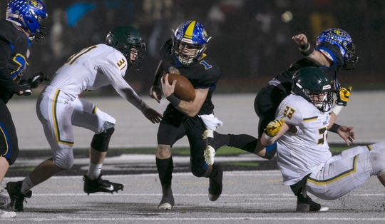 Sutter Union's Cory McIntyre, center, runs past Paradise's Josh Alvies, left, and Ashton Wagner, right, during the first quarter of a Northern Section Division III high school football playoff game in Yuba City, Calif., Saturday, Nov. 30, 2019. Paradise had an undefeated season and made it to the section championship game a year after the deadliest wildfire in California history that killed dozens and destroyed nearly 19,000 buildings including the homes of most of the players.