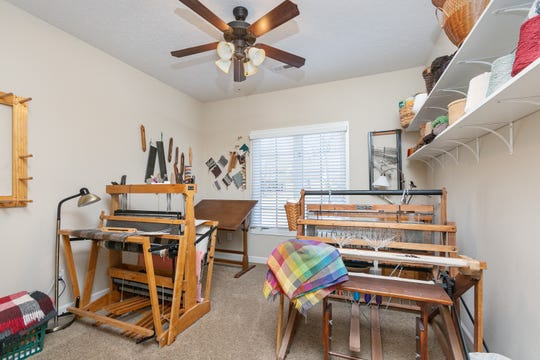Two of Jackie's three looms are found in her loom room. She says it's something she wanted to try in retirement and, evidently, it has worked out well. An example of her work can be seen folded over the loom on the right.