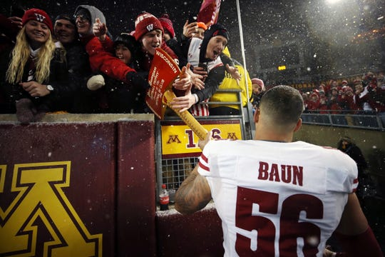 Wisconsin linebacker Zack Baun (56) holds out Paul Bunyan's Axe for fans to touch after Wisconsin beat Minnesota 38-17 in an NCAA college football game Saturday, Nov. 30, 2019, in Minneapolis. (AP Photo/Stacy Bengs)