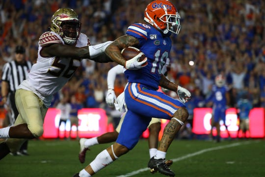 Nov 30, 2019; Gainesville, FL, USA; Florida Gators wide receiver Freddie Swain (16) runs for a touchdown against Florida State Seminoles linebacker Emmett Rice (56) during the first quarter at Ben Hill Griffin Stadium. Mandatory Credit: Kim Klement-USA TODAY Sports