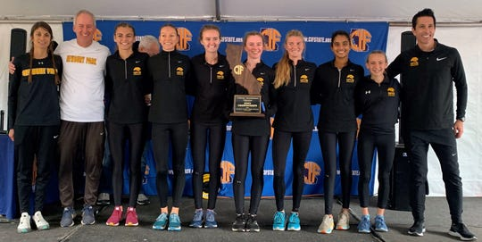 The Newbury Park High girls cross country team poses with the Division II state plaque after winning the program's first state crown Saturday in Fresno.