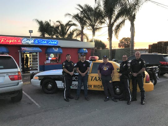 "Oxnard police officers pose in front of a ""Choose Your Ride"" vehicle outside Roger's Cafe in Oxnard on Nov. 22."