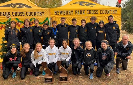 The Newbury Park boys and girls cross country teams pose with their state championship plaques on Saturday in Fresno.