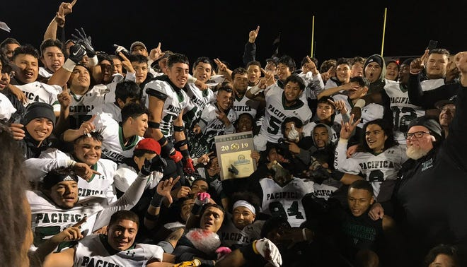 The Pacifica High football team poses with the CIF-Southern Section plaque after capturing the Division 6 championship with a 42-41 win against La Serna at California High in Whittier on Saturday night.