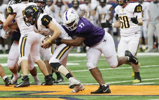 New Rochelle's Darren Kabba (77) sacks McQuaid quarterback Joe Cairns (7)  during the NYSPHSAA Class AA state championship at the Carrier Dome in Syracuse Nov. 30, 2019. New Rochelle won the game 28-0.
