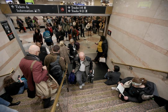 People sit on stairs as they wait for their homebound NJ Transit trains at Penn Station during the evening commute Nov. 27, 2019.