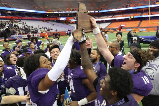 New Rochelle players celebrate with the championship plaque after defeating McQuaid in the NYSPHSAA Class AA state championship at the Carrier Dome in Syracuse Nov. 30, 2019.
