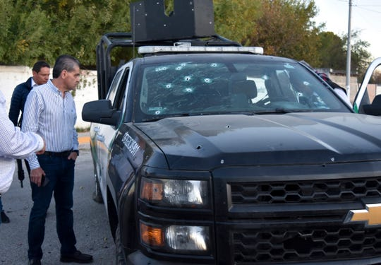 Coahuila state Governor Miguel Riquelme Solis looks at a police vehicle shot during a gunbattle between Mexican security forces and suspected cartel gunmen in Villa Union, Mexico, Saturday, Nov. 30, 2019.