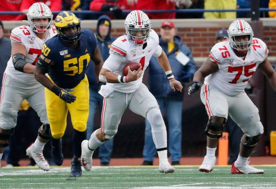 Ohio State quarterback Justin Fields runs for yardage against Michigan during the second half at Michigan Stadium.