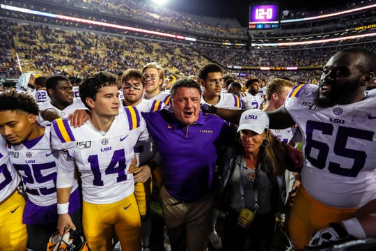 LSU coach Ed Orgeron celebrates with his players after defeating Texas A&M Aggies at Tiger Stadium.
