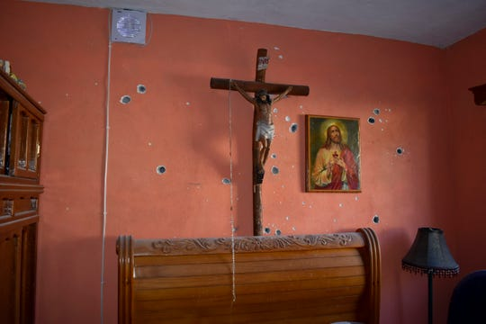 A wall of the room of a home is riddled with bullet holes after a gun battle between Mexican security forces and suspected cartel gunmen, in Villa Union, Mexico, Saturday, Nov. 30, 2019.