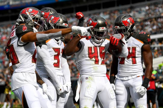 Buccaneers linebacker Devin White (45) celebrates with teammates after an interception during the first quarter against the Jaguars at TIAA Bank Field.