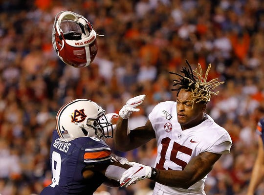 Auburn's Shaun Shivers, left, knocks the helmet off Alabama's Xavier McKinney as he rushes for a touchdown in the second half at Jordan Hare Stadium on November 30, 2019 in Auburn, Alabama.