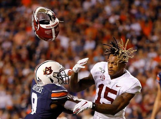 Auburn's Shaun Shivers, left, knocks the helmet off Alabama's Xavier McKinney as he rushes for a touchdown in the second half at Jordan Hare Stadium on November 30, 2019 in Auburn, Alabama.