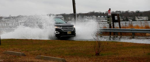 A car plows through high water from the Toms River along Riverside Drive in Pine Beach Monday afternoon, December 2, 2019.