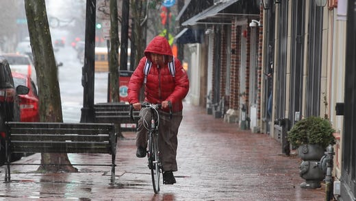 A man rides his bike along Broad Street as snow begins to fall around 11:30am in Red Bank, NJ Monday December 2, 2019.