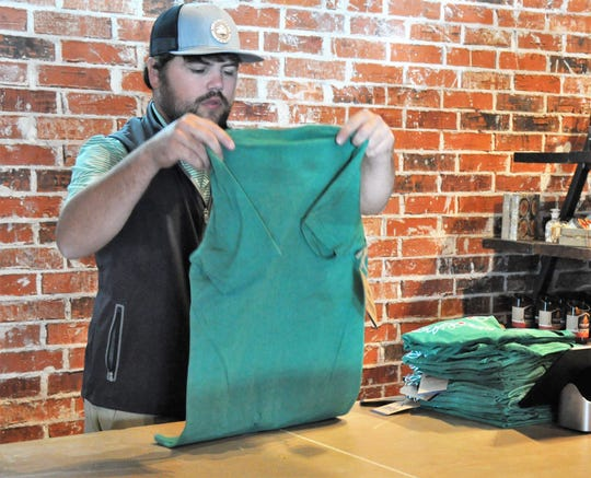 Tanner Evans folds shirts at Circle T Outfitters on Nov. 19. The back half of the apparel lifestyle store offers beer-and-wine service, which is a strategy to increase store foot traffic.