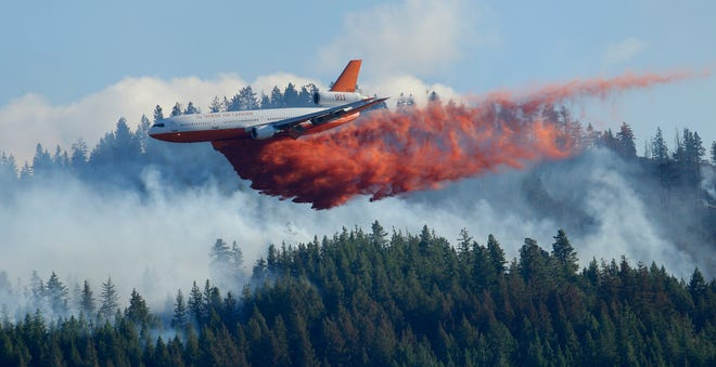 FILE - In this Aug. 21, 2015 file photo, a tanker airplane drops fire retardant on a wildfire burning near Twisp. The state's commissioner of Public Lands released a proposal Monday, Dec. 2, 2019, that provides some $63 million each year to fight wildfires and take steps to prevent them in the first place.