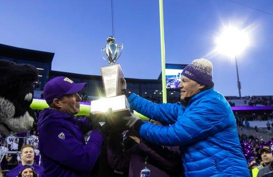 Washington Governor Jay Inslee hands Washington head coach Chris Petersen the Apple Cup after an NCAA college football game between Washington and Washington State, on Friday, Nov. 29, 2019 in Seattle. Washington won 31-13.